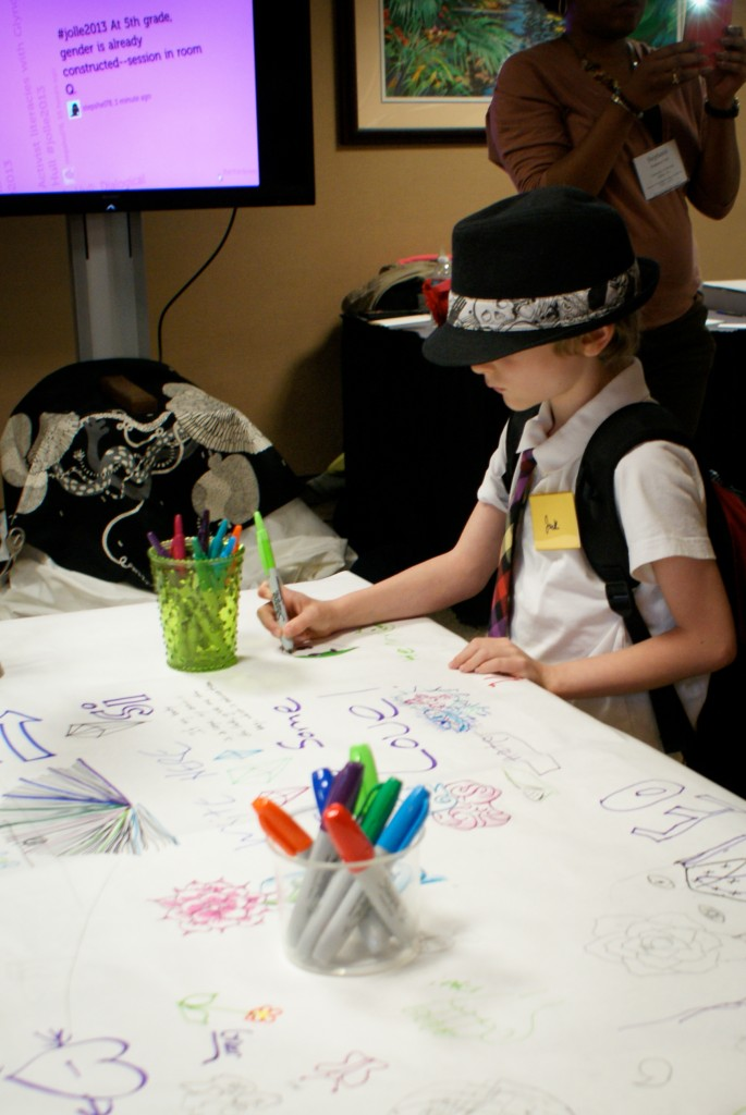 Photograph of young boy drawing on a large piece of paper.